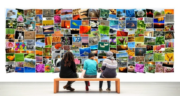 A wall of multicoloured pictures with three people sitting on a bench looking at the wall